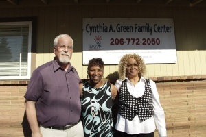 Cynthia Green (middle) stands under the new Cynthia A Green Family Center sign.