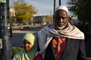 Zeytuna and Moalim Edo wait to cross street on MLK, not far from where Zeytuna was struck by a car in a hit-and-run accident.