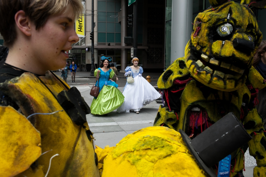 "Sarah Kauppila of Enumclaw, dressed as Cinderella, and her mother, Luanne Kauppila, dressed as one of Cinderella's evil step-sisters Griselda, make their way into GeekGirlCon on Sunday, October 9, 2016 at the Washington State Convention Center in downtown Seattle.   In the foreground, Kaitlynne Fowler, left, chats with her twin, Makenna Fowler. The pair are dressed as characters from the video game ""Five Nights at Freddy's."""