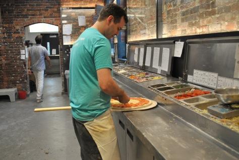 Pagliacci cook prepares pizza