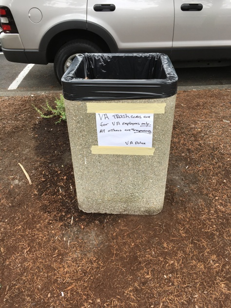 Image 1 Caption--Trashbins on the VA Medical Center grounds carry a warning.