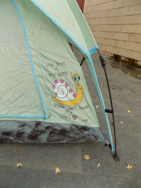 Image 3 Caption--A tent in the encampment in front of city hall adorned with art.